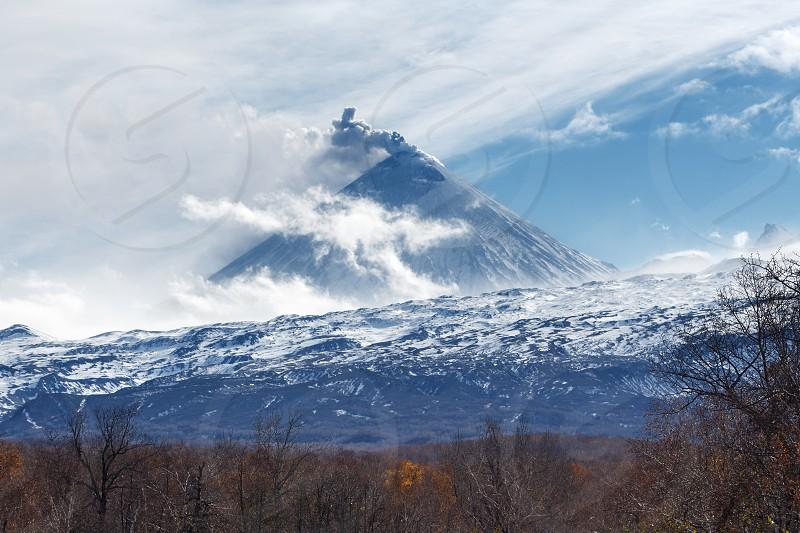 Kamchatka volcanic landscape: view of explosive-effusive eruption Klyuchevskoy Volcano (Klyuchevskaya Sopka) on a sunny weather. Russian Far East Klyuchevskaya Group of Volcanoes. photo