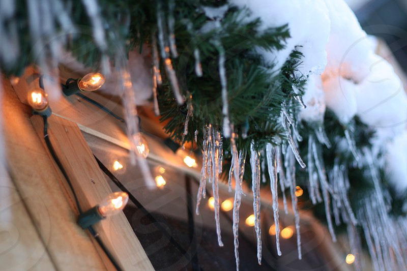 frozen icicles and white string lights outdoors on wooden home photo