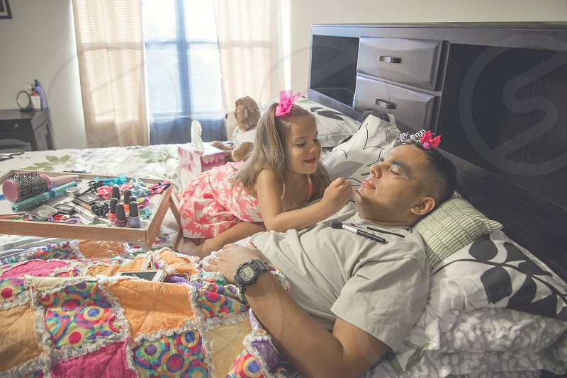 girl in pink dress putting makeup on sleeping man in gray shirt lying on bed photo