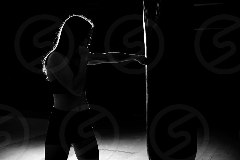 Silhouette of a young girl training kickbox and punching boxing bag. photo
