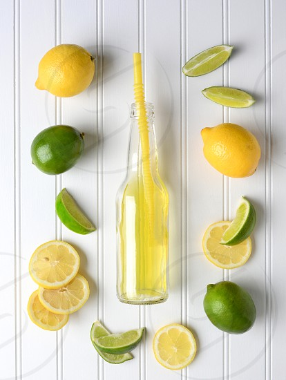 Limes and Lemons surrounding a bottle of soda on a white bead board table. High angle shot in vertical format. photo