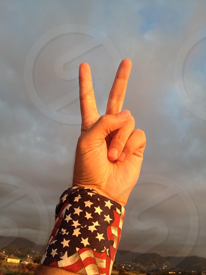 person with us flag handkerchief wrapped around wrist doing peace hand sign photo