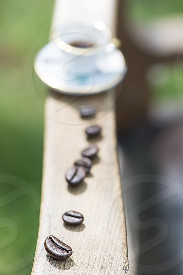 Cup of coffee on wooden table. Small miniature cup photo