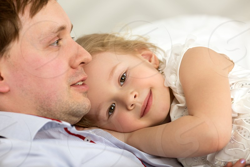 Little daughter lying on fathers chest. She showing her devotion to dear dad photo