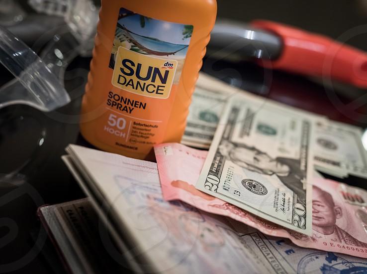 Passport money sun protection sun cream diving travel stamps thai baht us dollar snorkel photo