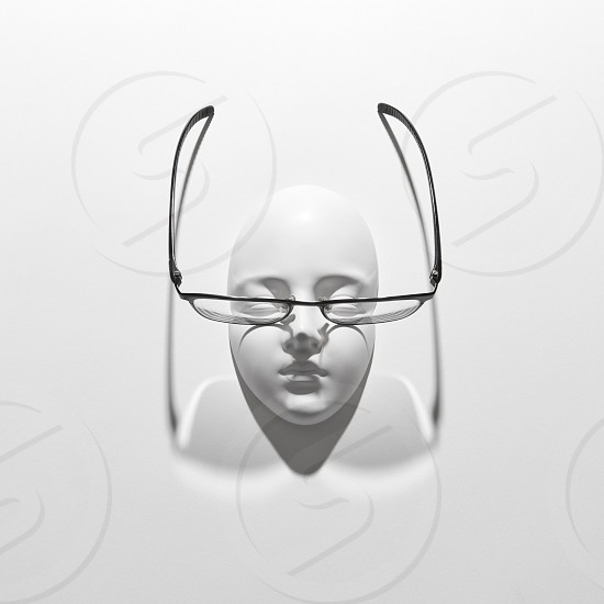 Glasses with plaster mask face for person with visual impairment long shadows on a white background copy space. Top view. Optics fashion healthy lifestyle. photo