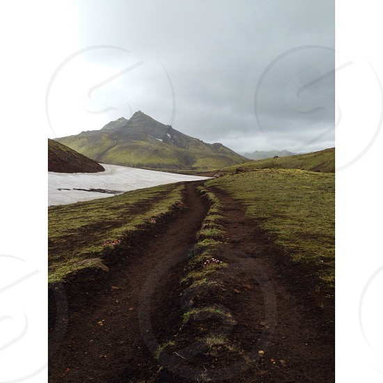 view of green mountain under dark clouds photo