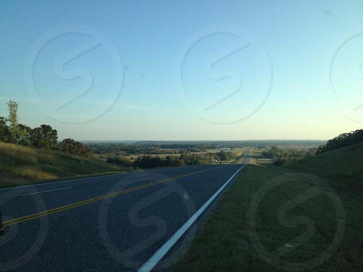 green grass field beside gray rolled asphalt road photo