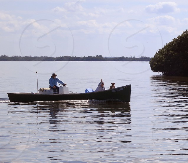 People and dog exploring Florida waters in motor boat photo