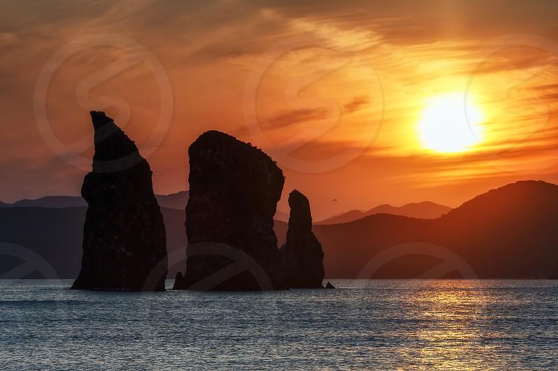 Kamchatka seascape: beautiful view of Three Brothers Rocks in Avachinskaya Bay (Pacific Ocean) at sunset. Kamchatka Peninsula Russian Far East Eurasia. photo