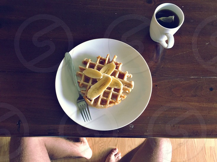 sliced bananas on a waffle with a silver fork on a white plate next to tea in a mug on a wood table photo