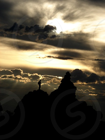 man on top of rock formation silhouette photo
