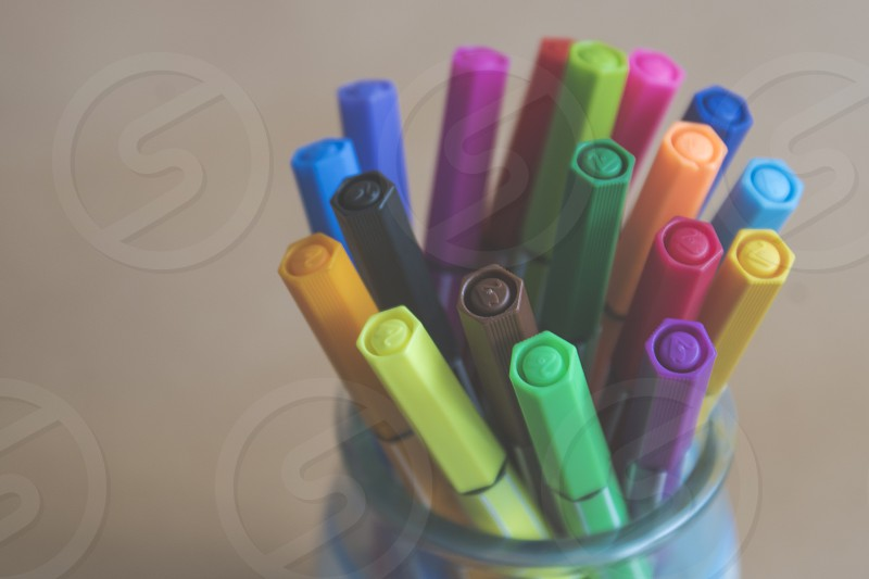 colored pens in clear glass jar photo
