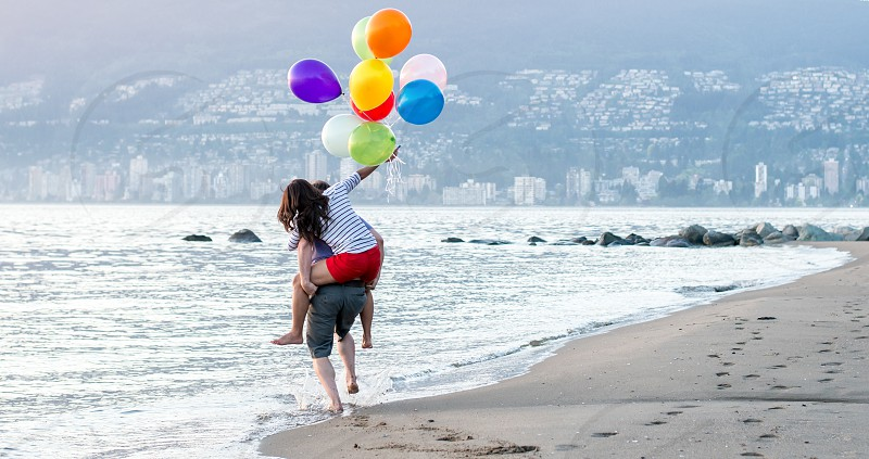 woman riding on the man's back while holding multicolored balloon photo