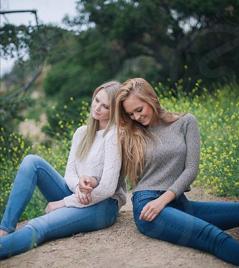 Togetherness together sisters rock meadow flowers relaxing spring springtime jeans sweaters trees love cute photo