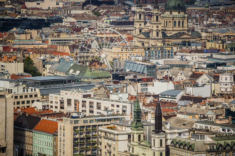 Aerial view of Sziget's Eye (ferris wheel) and St. Stephen's Basilica with many rooftops. photo