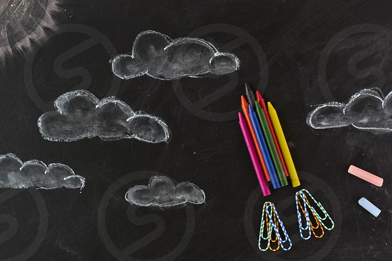 Rocket made out of crayons. on a blackboard. photo