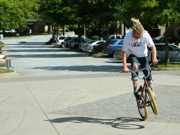 man riding BMX doing tricks during daytime photo