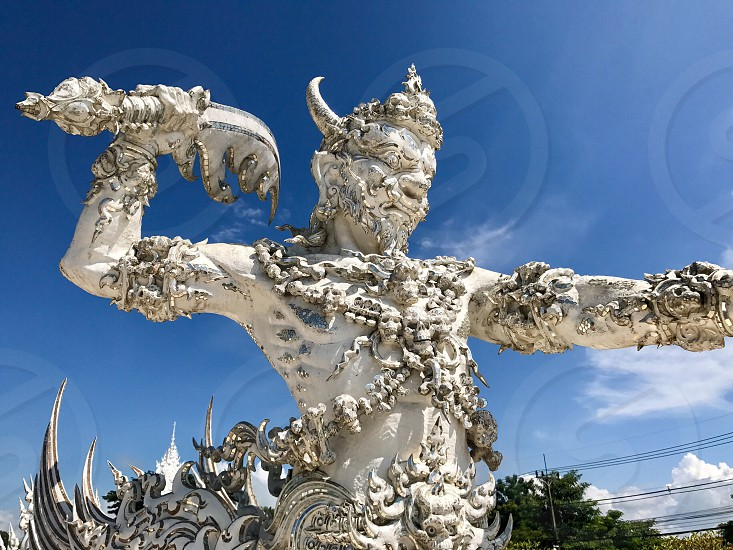Outdoor day landscape horizontal colour Wat Rong Khun The White Temple Chiang Rai Thailand Thai Kingdom of Thailand travel tourism tourist wanderlust summer summertime temple Buddhist Buddhism spiritual pure holy dragon monster carved ornate elaborate art modern sculpture sculpted east eastern hands silver mirror mosaic magical stretch stretched warrior attack mythical skulls blue sky photo
