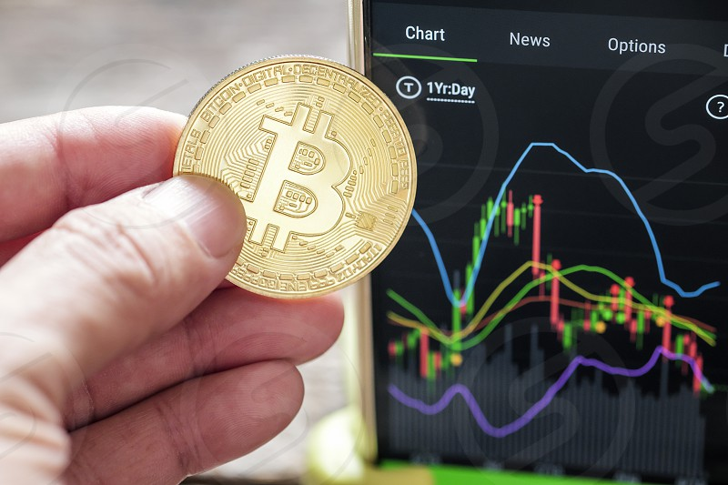 Close-up of hand holding Bitcoin with graph chart in the background. Shallow depth of field. photo