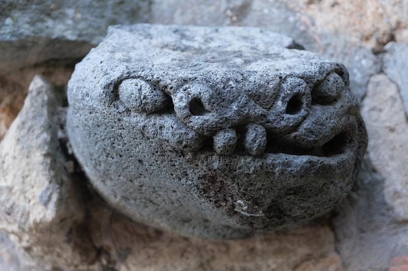 Ornamental carved stone object on facade house Civita di Bagnoregio Italy photo