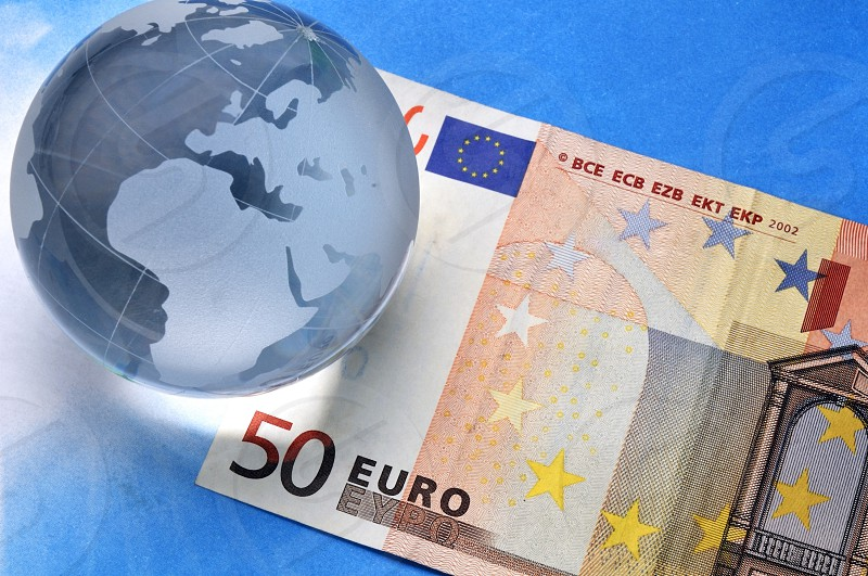 Earth globe with Euro banknote over blue paper background. photo
