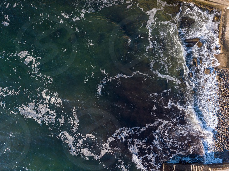 Natural marine seascape with turquoise color of water and stone beach in a summer day. White foam waves pattern . Copy space. Aerial top view from drone. photo