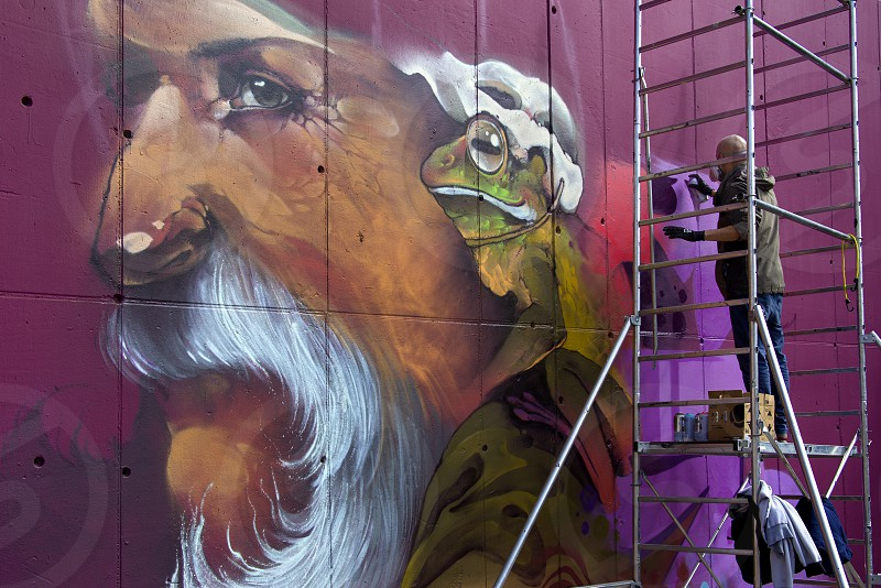 Artist in the process of drawing graffiti on the wall of a multi-storey building photo