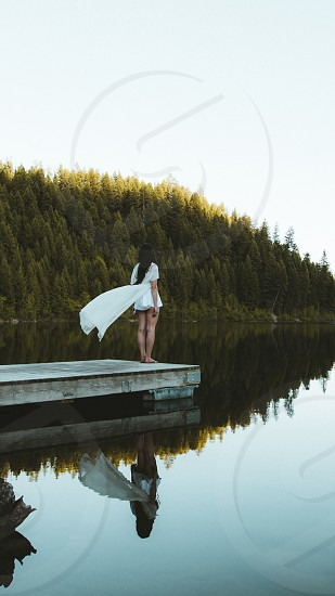 Girl standing on dock overlooking perfectly still lake. photo