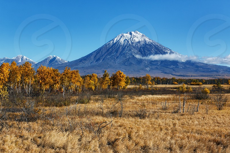 Kamchatka Peninsula landscape: beautiful autumn view of active Koryak Volcano and blue sky on sunny day. Avachinsky-Koryaksky Group of Volcanoes Kamchatka Region Russian Far East Eurasia. photo