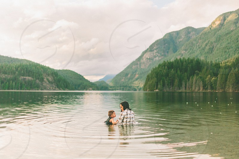 A mother and son sitting in a lake fully clothed.  photo