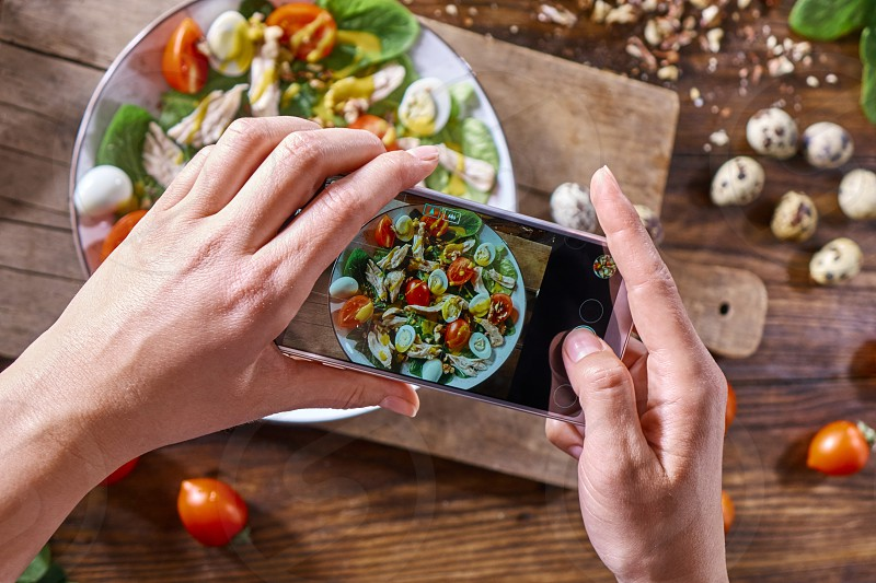 On the kitchen table on a wooden board a plate with homemade salad. Woman's hands with a phone make photo of salad. photo