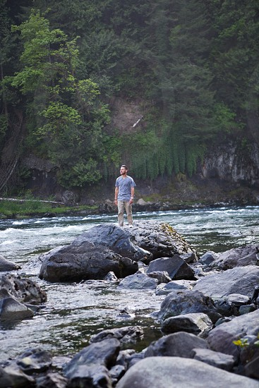 man standing in the middle of river photo