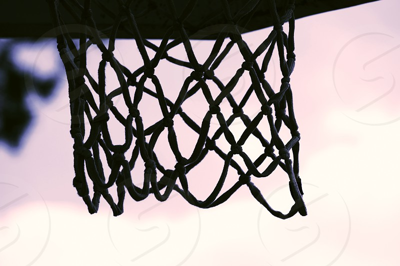 Basketball net silhouette closeup against sky. photo