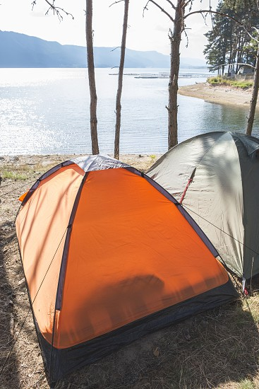 Tents in the forest in front of mountain lake  photo