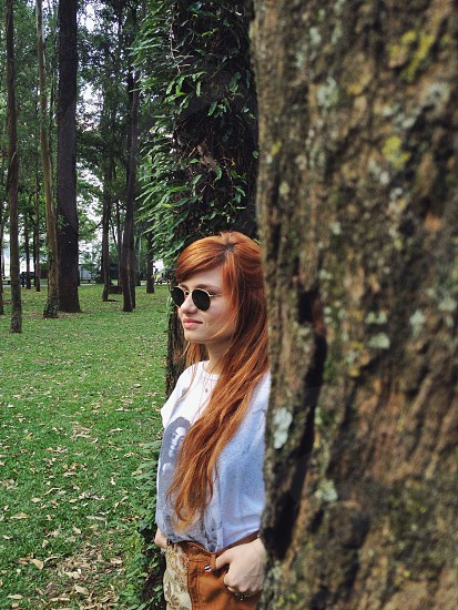 woman in black sunglasses and gray shirt standing in between trees photo