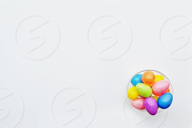 Small bowl of colorful Easter eggs sit in a corner of a white background photo