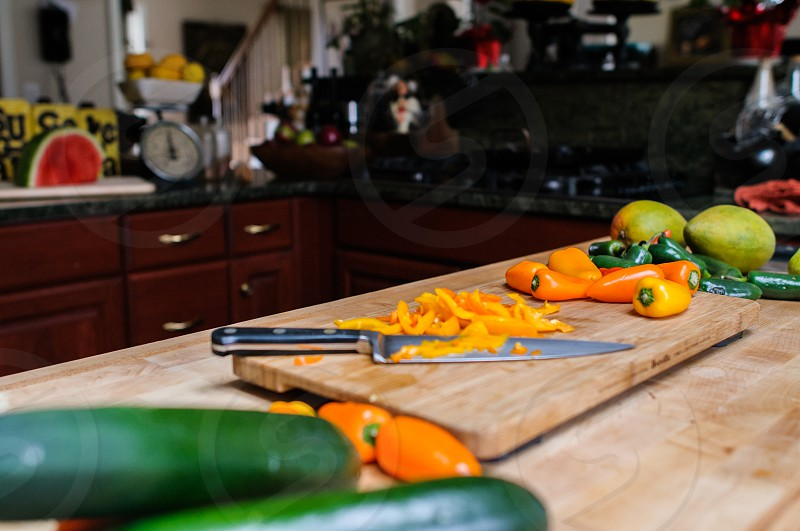 peppers mangoes and cucumbers on a wood cutting board photo
