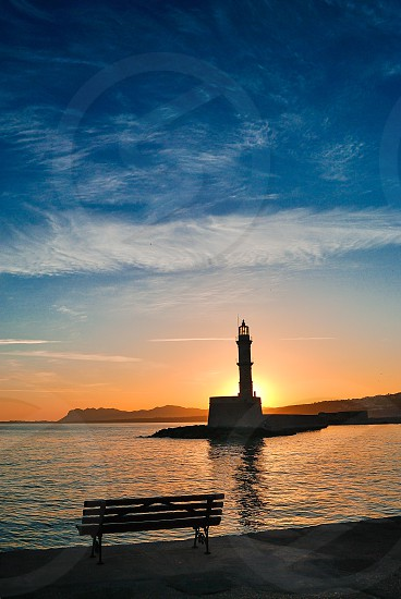 Sunrise behind the lighthouse at the port of Chania in Crete Greece photo