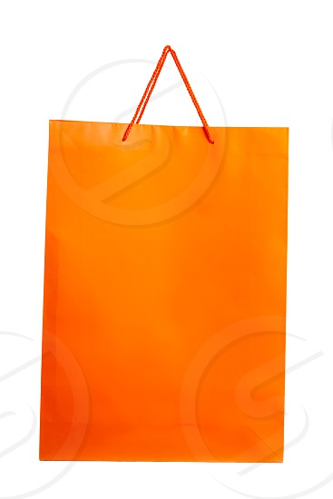 Orange paper bag isolated on white. Front angle. photo