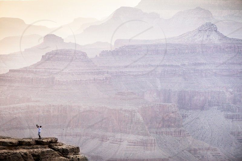 A lone explorer takes a selfie while standing on a  ledge at the Grand Canyon AZ. photo