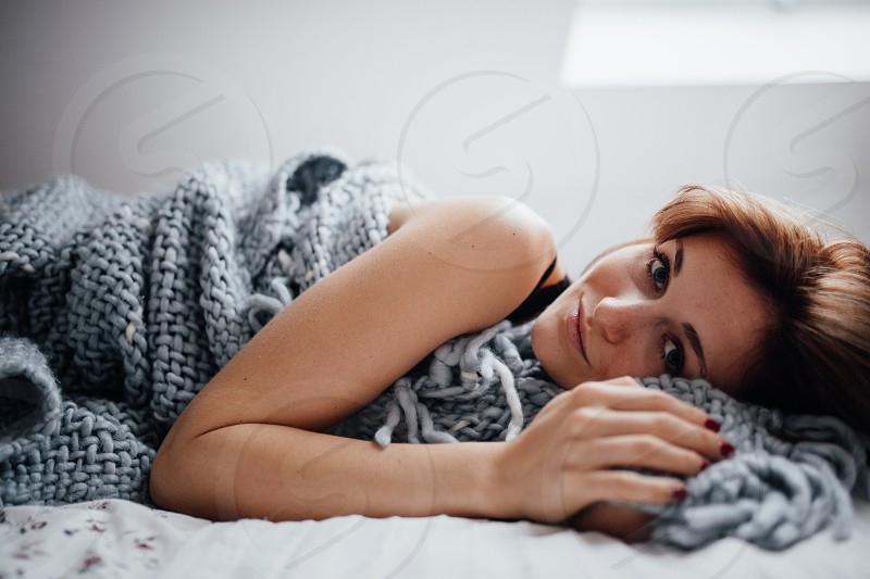 Young caucasian women laying in bed looking at camera  photo