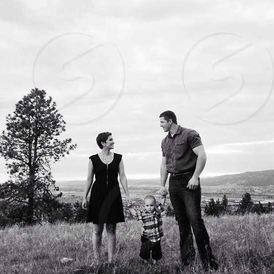 man woman and child on a grassy field black white photo photo