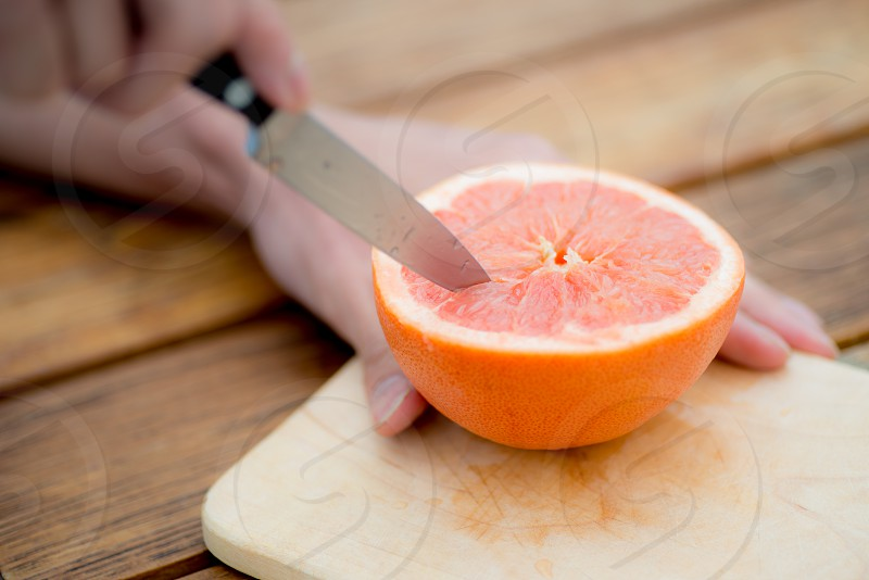 person slicing orange fruit on brown wooden cutting board in tilt shift lens photo
