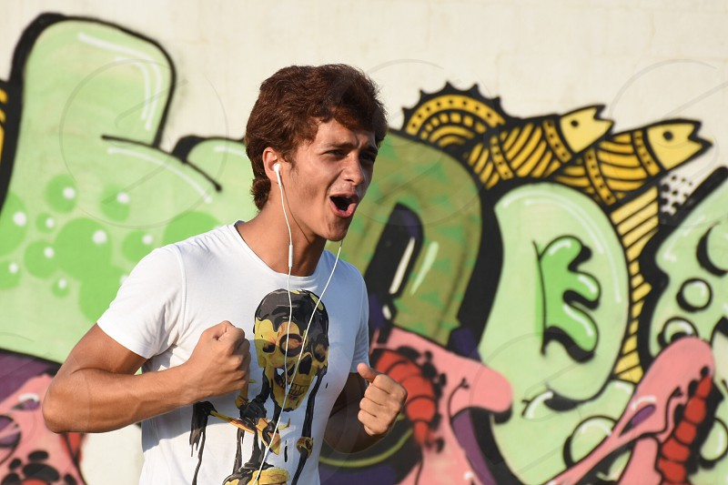 man in white t shirt using white earbuds while running photo