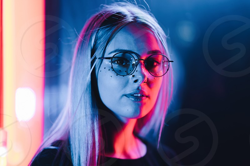 Millennial enigmatic pretty girl with unusual dyed hairstyle near glowing neon wall at night. Blue hair golden sequins as frecklesnose piercing. Mysterious hipster teenager in glasses. photo
