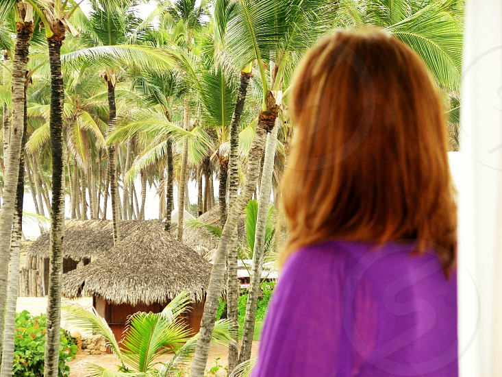 Beautiful redhead overlooking beach huts and palm trees in the Dominican Republic photo