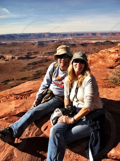 man and woman sitting on rocky mountain photo