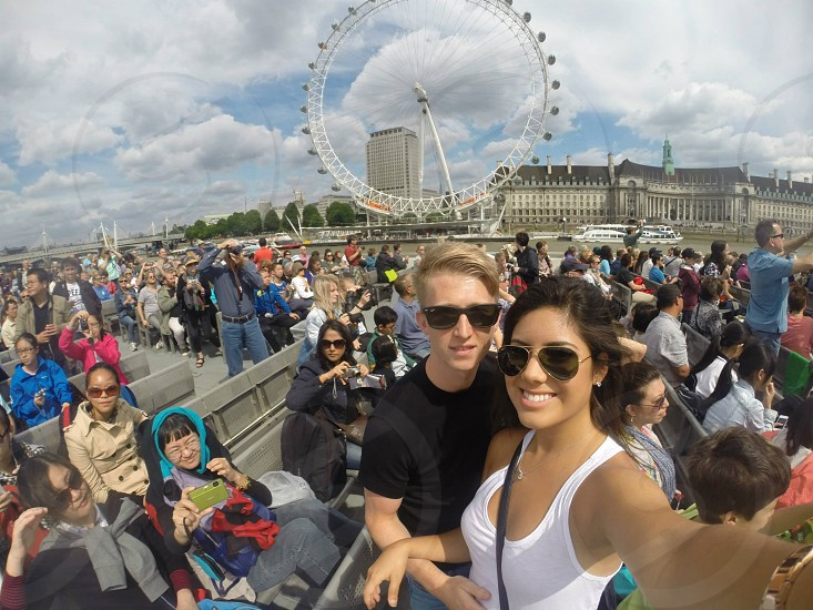 180 degree lens photography of woman in white tank top smiling together with man in black crew-neck t-shirt with London Eye London photo