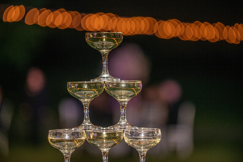 Champagne glasses stacked up into a pyramid photo